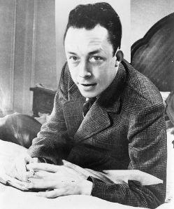 499px-Albert_Camus%2C_gagnant_de_prix_Nobel%2C_portrait_en_buste%2C_pos%C3%A9_au_bureau%2C_faisant_face_%C3%A0_gauche%2C_cigarette_de_tabagisme